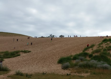People walking up a sand dune