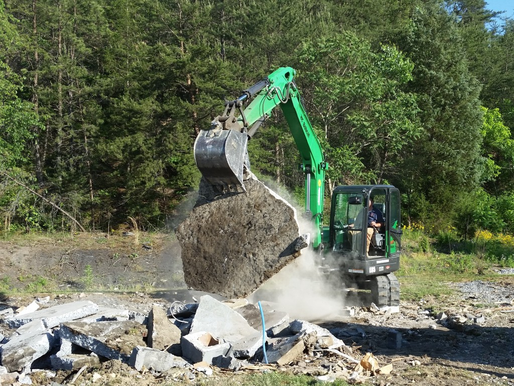 Backhoe digging through concrete
